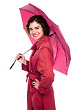 Glamorous woman standing under pink umbrella