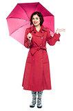 Woman under umbrella trying to feel rain