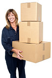 Friendly delivery woman with three packed cartons