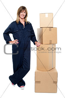 Beautiful delivery woman standing beside cartons