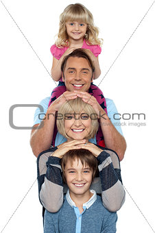 Attractive smiling family of four posing in a single line