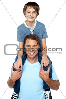 Adorable young son enjoying piggyback ride