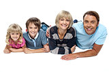 Smiling family of four relaxing on white background