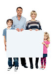 Active young family displaying blank ad board