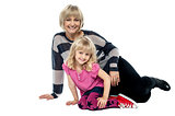 Cheerful mum and daughter sitting on studio floor