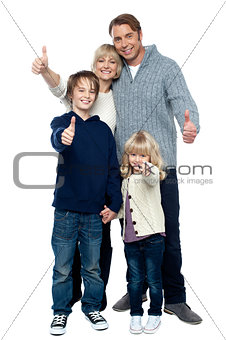 Adorable family in winter clothes gesturing thumbs up