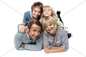 Adorable young kids piled on top of their parents