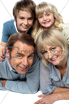 Parents lying down with children on top