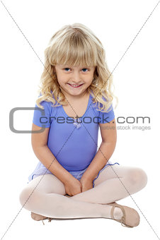 Adorable kid sitting with crossed legs on the floor