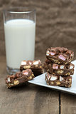 Rustic background with rocky road dessert squares with glass of milk