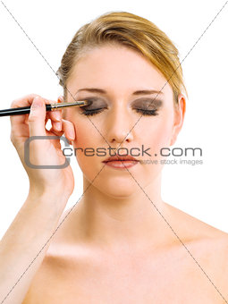 Applying makeup on beautiful model