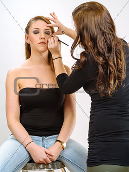 Applying eye makeup on beautiful model