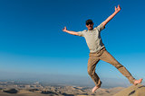man jumping in the desert of the peruvian coast at Ica Peru