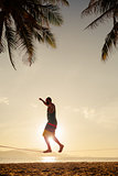 teenage balancing on slackline on the beach