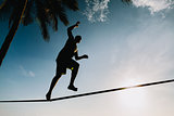 teenage balancing on slackline with sky view