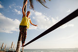 teenage girl  balancing on slackline with sky view
