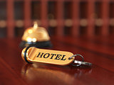 Room access key and bell on wooden reception desk. Soft focus il