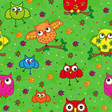 Seamless pattern with ornamental owls over green