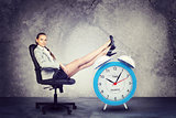 Businesswoman sits in chair. Put your feet up on big red alarm clock