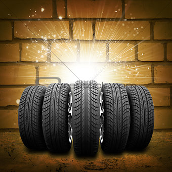 Car wheels. Background is brick wall, concrete floor and light at center