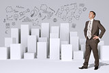 Businessman standing akimbo. Many white cubes with business sketches