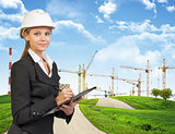 Businesswoman holding clipboard. Green hills, road and tower cranes as backdrop