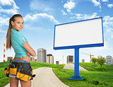 Girl builder in toolbelt. Large billboard, road, grass hills and city