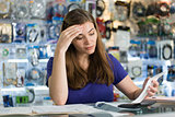 Worried Woman Checking Bills And Invoices In Computer Shop