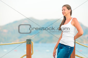 beautiful girl on the pier looks attentively aside