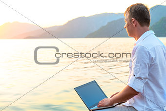 free man with a laptop admires dawn