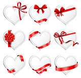 Festive heart-shaped  cards with red gift ribbons.