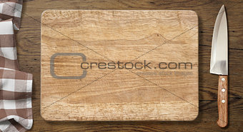 Cutting board and knife on old wood table with picnic tablecloth