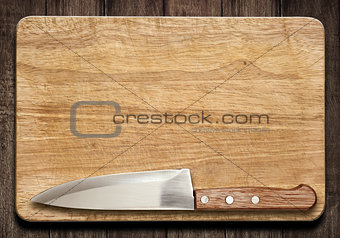 Cutting board and knife on old wood table