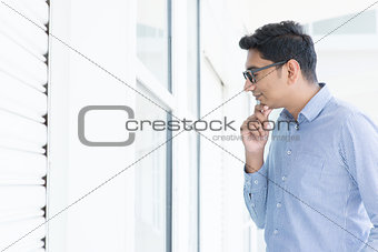Asian man looking through the window