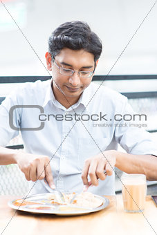 Handsome man eating food at cafeteria.
