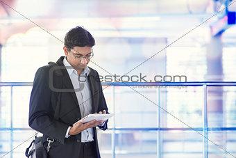 Man using tablet computer at train station