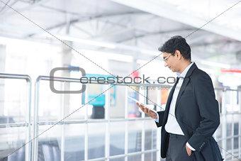 Man using tablet computer at railway station