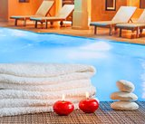 Spa massage border background with towel stacked,red candles and stone near swimming pool