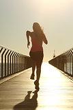 Runner silhouette running fast at sunset