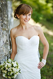 Gorgeous young bride enjoying wedding day. Summertime newlywed.
