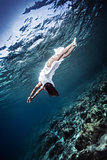 Active woman diving to the sea bottom