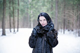 Girl wearing a fur coat in winter forest