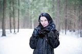 Girl wearing a fur coat in winter forest