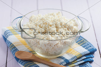 Cottage cheese in a glass with a wooden spoon, close-up, selecti