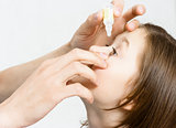 hand dripping drug solution in the eyes of a child