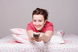 young girl is watching TV in bed