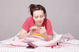 Girl enthusiastically saws, nails lying in bed