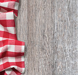rough wood kitchen table with red picnic cloth background
