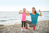 Healthy mother and baby girl showing biceps on beach