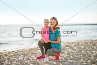 Portrait of healthy mother and baby girl on beach in the evening